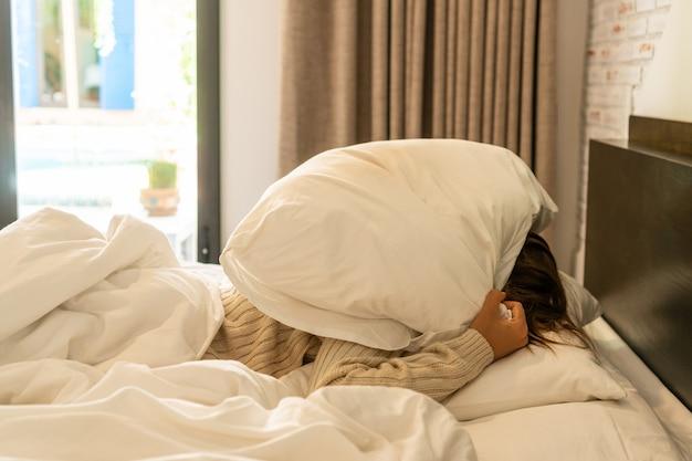 Jovem bela mulher asiática odeia acordar de manhã cedo. menina com sono tentando se esconder debaixo do travesseiro