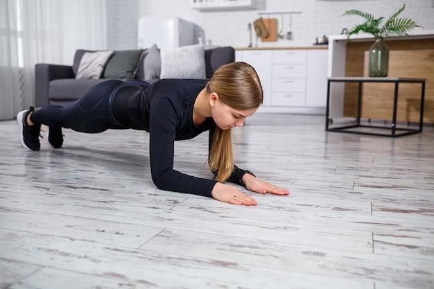 Jovem bela mulher atlética em leggings e top fazendo os exercícios de prancha. estilo de vida saudável. a mulher pratica esportes em casa.