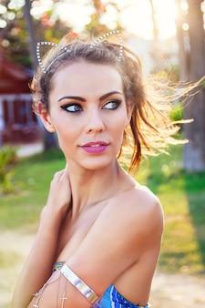 Jovem bela mulher bronzeada sexy posando em um país tropical quente em suas férias. usando maquiagem brilhante. cores do sol.