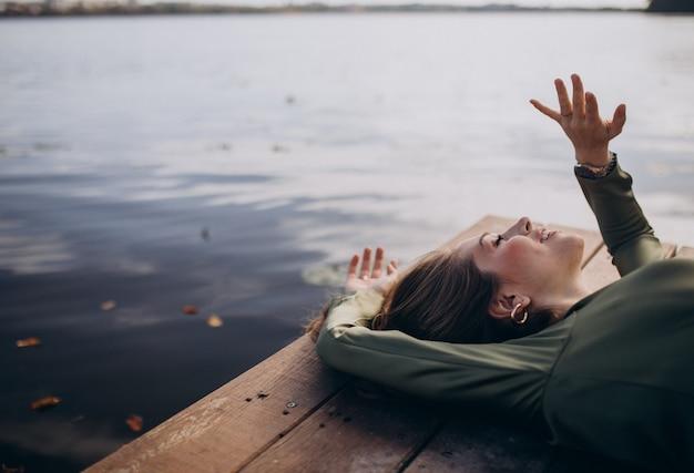 Jovem bela mulher deitada à beira do lago