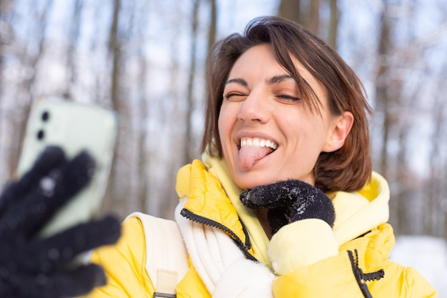 Jovem, bela mulher feliz e alegre no videoblog da floresta de inverno, faz uma foto de selfie