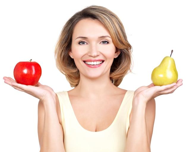 Jovem bela mulher feliz mantém a maçã e a pêra isoladas em branco.