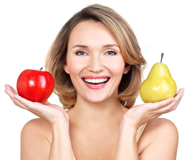 Jovem bela mulher feliz segura a maçã e a pêra - isoladas no branco.