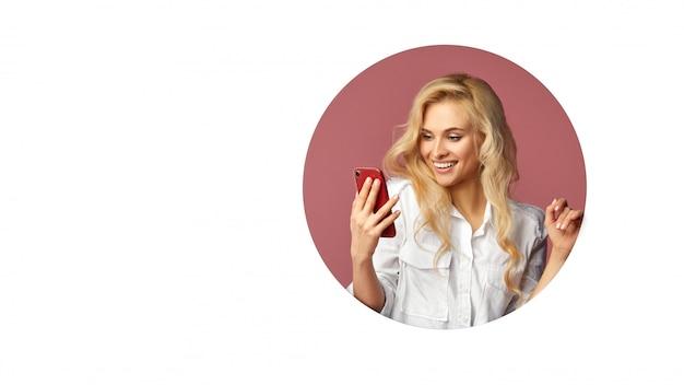 Jovem bela mulher feliz usando um smartphone. espreita para fora de um buraco redondo na parede. parede branca. espaço vazio para o texto.