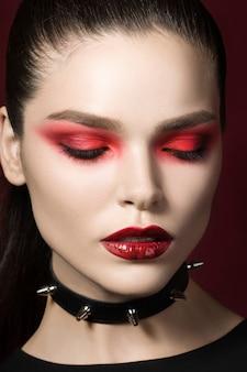 Jovem bela mulher gótica com lábios vermelhos de pele branca, colarinho preto com pontas. olhos vermelhos esfumados.