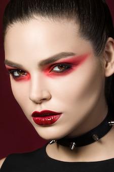 Jovem bela mulher gótica com pele branca e lábios vermelhos com gotas de sangue usando colarinho preto com pontas. olhos vermelhos esfumados.