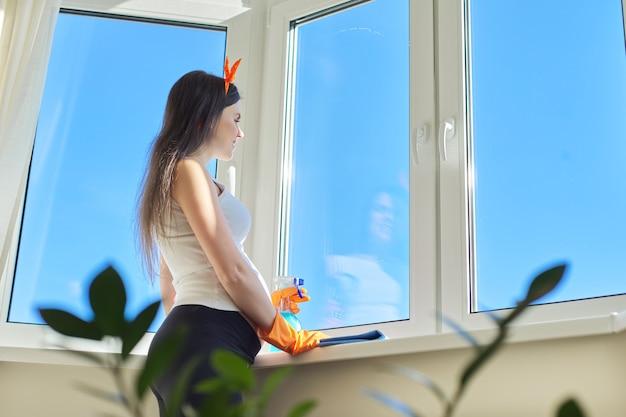 Jovem bela mulher grávida sorridente em luvas com detergente e pano, olhando para janela limpa e lavada, copie o espaço. limpeza do apartamento, preparação da casa para o aparecimento do bebê