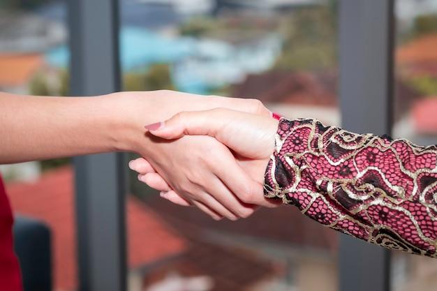 Jovem bela mulher muçulmana, apertando a mão com amizades caucasianas