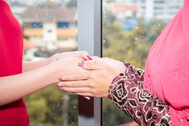 Jovem bela mulher muçulmana, apertando a mão com amizades caucasianas.