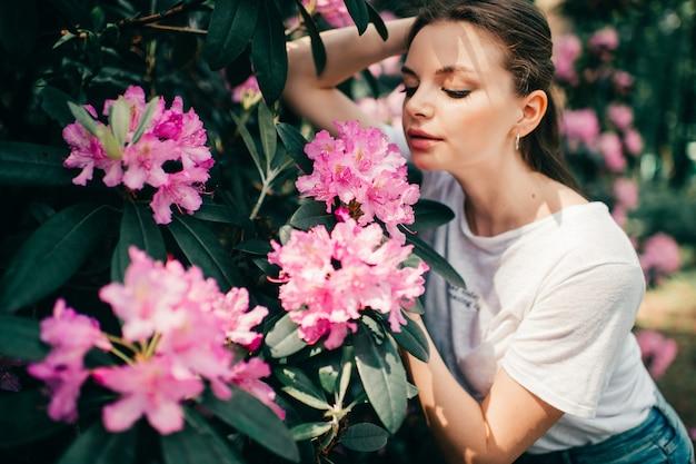 Jovem bela mulher posando entre a árvore florida