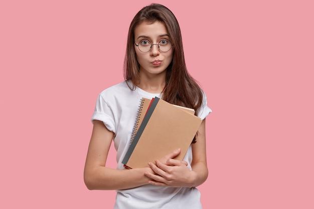 Jovem bela mulher séria tem cabelo escuro, carrega cadernos de espiral, vestida de camiseta branca, óculos, pressiona os lábios