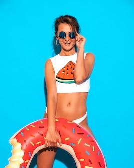 Jovem bela mulher sexy sorridente em óculos de sol. garota de cueca branca de verão e tópico com colchão inflável donut lilo.