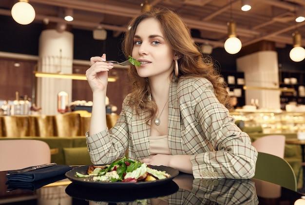 Jovem bela mulher sorridente, comer alimentos saudáveis