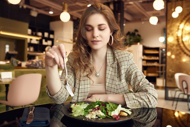 Jovem bela mulher sorridente, comer alimentos saudáveis Foto Premium