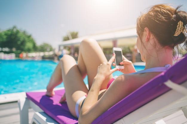 Jovem bela mulher sorridente em biquíni na piscina quente no resort e falar no celular.