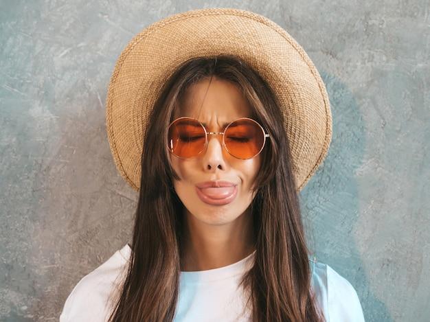 Jovem bela mulher sorridente olhando. menina na moda em roupas de verão casual camiseta e chapéu ... mostrando a língua