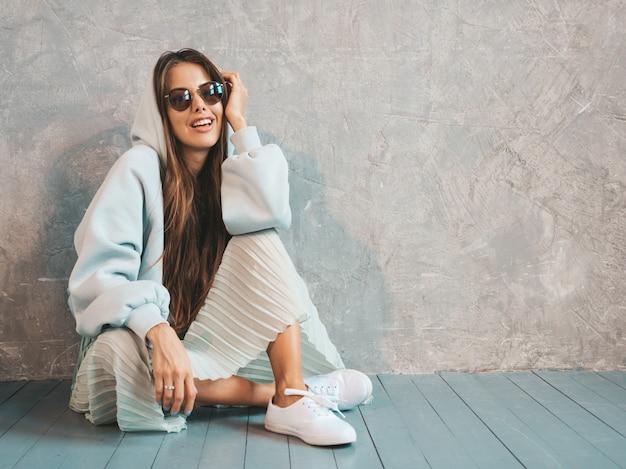 Jovem bela mulher sorridente olhando. menina na moda em roupas de verão casual capuz e saia. sentado no chão