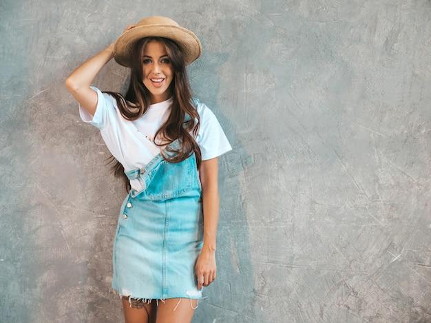 Jovem bela mulher sorridente olhando. menina na moda em roupas de verão casual macacão e chapéu.