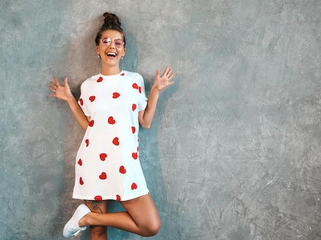 Jovem bela mulher sorridente olhando. menina na moda em verão casual branco vestido e óculos de sol.