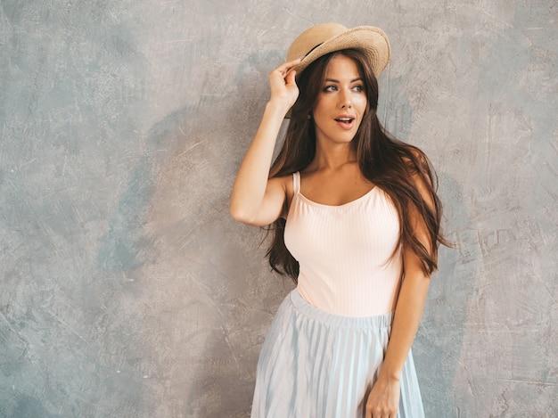 Jovem bela mulher sorridente olhando. menina na moda em verão casual vestido e chapéu.