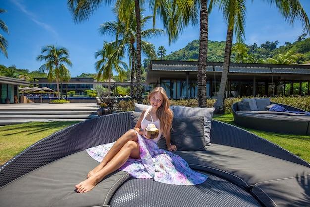 Jovem bela mulher sorridente segurando coco e relaxante
