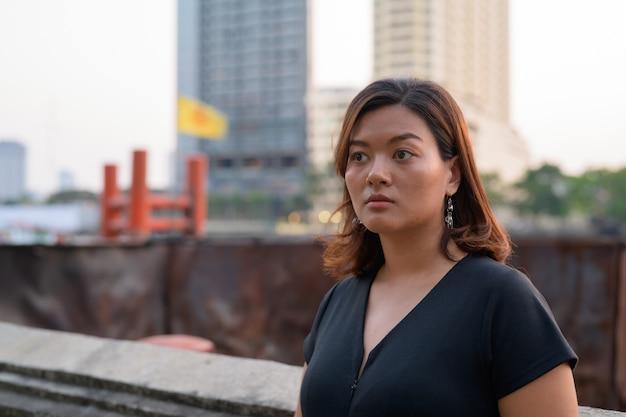 Jovem bela turista asiática pensando no cais à beira do rio