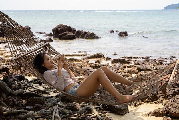 Jovem bela turista asiática relaxando na praia