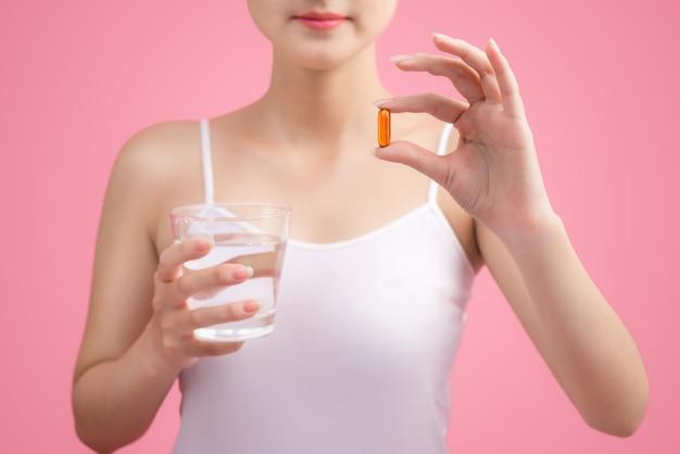 Jovem beleza asiática comendo comprimidos e bebendo água no fundo rosa.