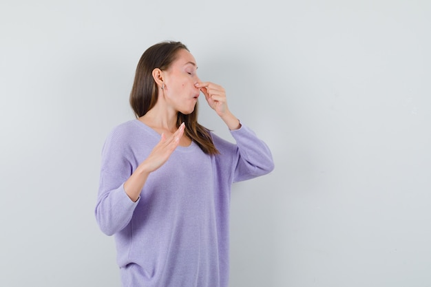 Jovem beliscando o nariz com uma blusa lilás e parecendo enojada