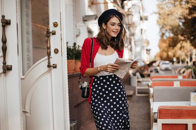Jovem bem construída com cabelo castanho, saia longa de bolinhas, blusa branca, camisa vermelha, boina e óculos andando pela cidade com mapa nas mãos e câmera durante o dia