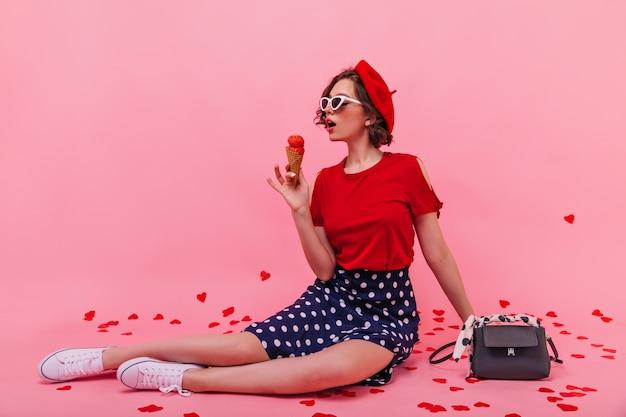 Jovem bem-humorada em sapatos desportivos brancos, posando com sorvete. senhora séria de boina sentada no chão e comendo sobremesa.