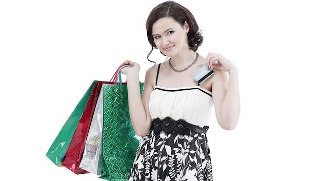 Jovem bem-sucedida com compras e cartão de crédito. isolada em uma parede de luz