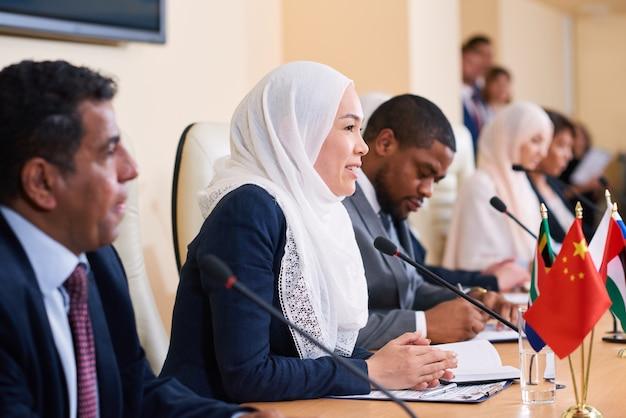 Jovem bem-sucedida delegada feminina em hijab participando da discussão do relatório do colega enquanto falava no microfone na conferência