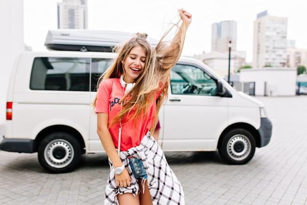 Jovem bem torneada com cabelo comprido dançando ao ar livre e relaxando com um sorriso e olhos fechados