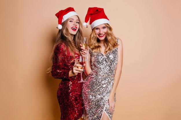 Jovem bem torneada com longos cabelos escuros usando um chapéu de ano novo segurando uma taça de vinho com um amigo