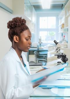 Jovem biólogo feminino africano trabalha no laboratório