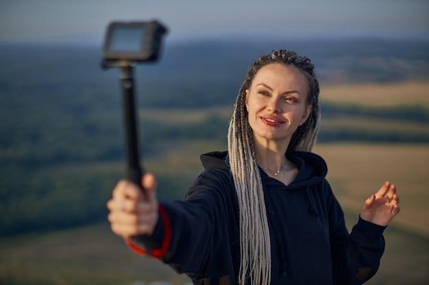 Jovem blogueira alegre tira uma selfie tira fotos de si mesma na câmera e se diverte stand ...