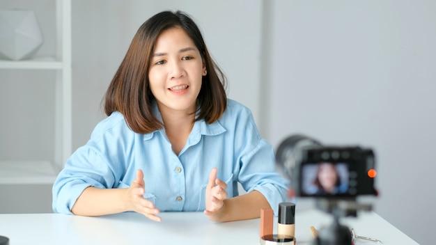 Jovem blogueira asiática gravando vídeo tutorial de maquiagem de produtos de beleza em casa