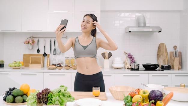 Jovem blogueira asiática usando selfie em smartphone na cozinha