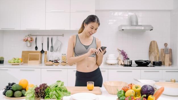 Jovem blogueira asiática usando smartphone para conversar, bater um papo e verificar mídias sociais na cozinha