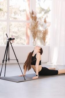 Jovem blogueira atlética em roupas esportivas balck grava vídeo no telefone enquanto faz exercícios em casa