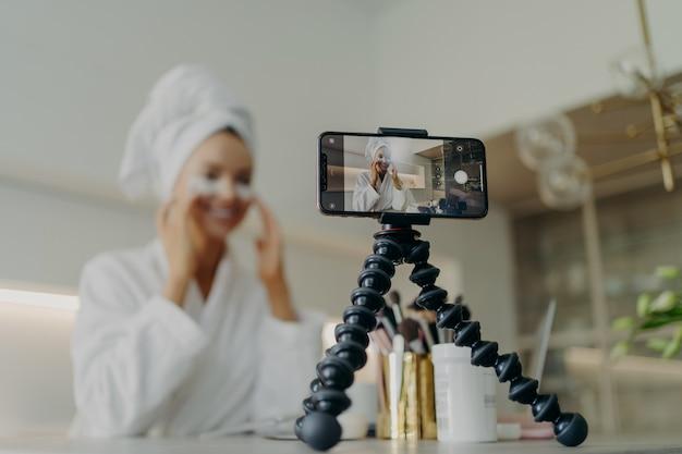 Jovem blogueira de beleza feliz vestindo roupão de banho, gravando um vídeo tutorial para cuidados com a pele. blog sobre o uso de adesivos cosméticos sob os olhos para tratar rugas e olheiras, foco na tela do smartphone