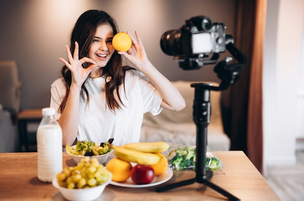 Jovem blogueira de comida cozinhando salada vegana fresca de frutas no estúdio de cozinha, tutorial de filmagem na câmera para canal de vídeo. uma influenciadora feminina segura laranja e fala sobre alimentação saudável.
