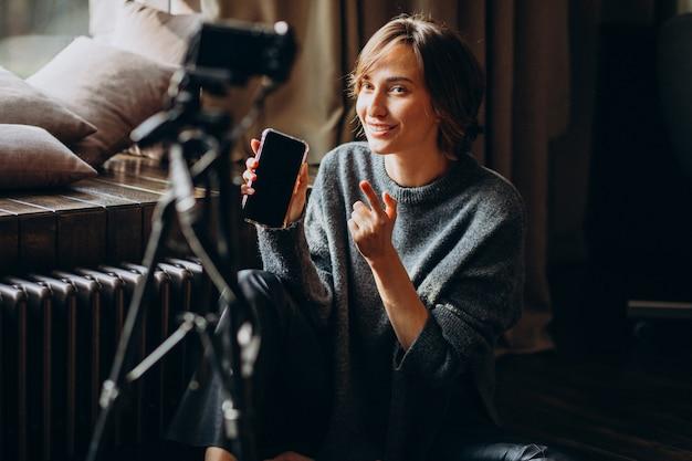 Jovem blogueira de vídeo fazendo uma revisão em vídeo para seu vlog