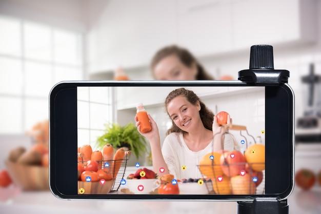 Jovem blogueira e vlogger e influenciadora online transmitem ao vivo um programa de culinária nas mídias sociais usando um smartphone