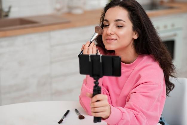 Jovem blogueira gravando a si mesma e colocando maquiagem