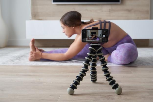 Jovem blogueira gravando vídeo de esportes em casa fazendo ioga na sala de estar