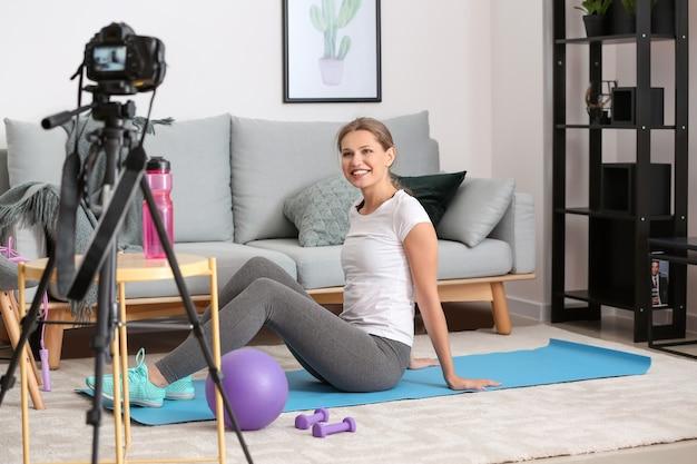 Jovem blogueira gravando vídeo de esportes em casa