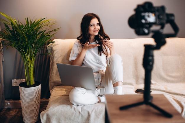 Jovem blogueira sorridente está sentada no sofá com o laptop segurando um doce e gravando seu vlog. blogging indoor.