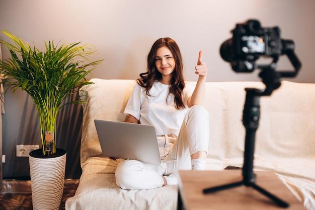 Jovem blogueira surpresa está sentada no sofá com o laptop gravando seu vlog de discurso para o público. blogging indoor. transmissão ao vivo.